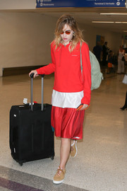 Suki Waterhouse made her way through the airport lugging a big black rollerboard.