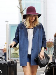 Suki Waterhouse was spotted at Heathrow wearing a cute burgundy sun hat.