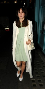 Suki Waterhouse teamed conservative white pumps with a mint-green dress and a silk coat for a night out.