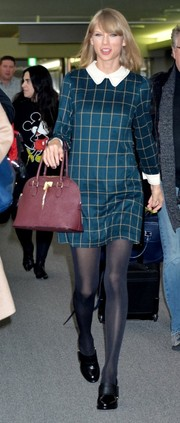 Taylor Swift landed at Narita International Airport looking charming in a collared teal grid-print mini by Miss Patina.
