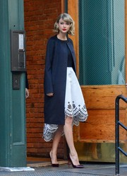 Taylor Swift stepped out in NYC wearing a boxy navy wool coat over a super-sweet cocktail dress.