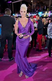Brigitte Nielsen wore this outrageous purple evening gown loud and proud! It was not short of details between a long-sleeve peek-a-boo shoulder, dramatic hemline, and beading!