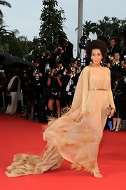 Solange Knowles chose this flowing nude dress that featured feather detailing on the skirt and a belted waist for her boho-inspired red carpet look.