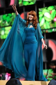 Florence Welch stunned in a deep sky blue strapless column dress and a matching flowing cape.