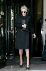 Charlize Theron traveled light to the Christian Dior show carrying a small black leather quilted clutch.