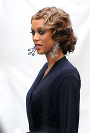 "Tyra attended a flapper-themed party for her guest appearance on ""Gossip Girl"" and she pulled off this themed look with ease. Her retro finger-waved updo and dramatic makeup looked amazing and check out those earrings!"