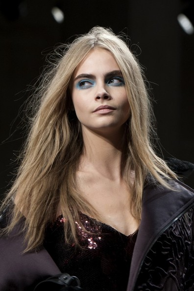 Cara Delevingne had her eyelids painted with blue eyeshadow at the Unique show at LFW.