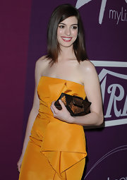 This copper buckle clutch is just the right complement to Anne's marigold strapless dress by Lela Rose.