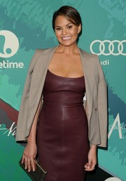 Chrissy Teigen toned down the sexiness of her leather dress with a taupe Vivienne Westwood blazer during the Power of Women event.