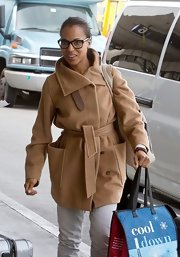 Kerry bundled up for the airport in this cozy camel wrap coat with large patch pockets.