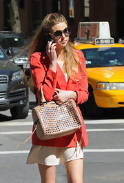 "Whitney showed off her city style while filming ""The City"". She paired a bright orange blazer with a nude dress and a killer studded tote bag."