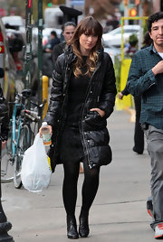 Olivia Wilde bundled up in a black down coat over her brocade dress while taking a break from filming 'The Longest Week.'