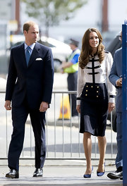 Prince William wore a classic navy suit with a light blue checkered tie for his and Kate's visit to Birmingham.