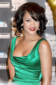 Showing off some luscious curls, Rihanna made a bold appearance in a green draped dress. She added major contrast to her look with red lips and jet-black curls.