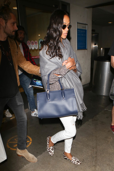 Zoe Saldana arrived on a flight at LAX wearing ripped white jeans and a print blouse.