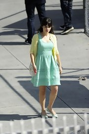 Zooey Deschanel chose a yellow cardigan to pair over her day dress for a bright and summery look.