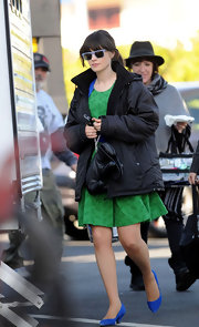 Zooey Deschanel kept warm in a summery frock by layering it with a black down jacket.