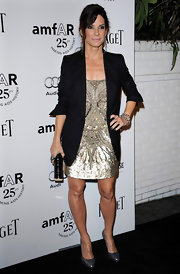 Sandra Bullock upped the shine of her stunning beaded dress with a gold hard case clutch.