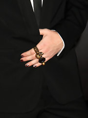 Adam wears an edgy skull ring, in gold.