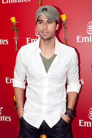 Enrique sported a distressed olive baseball cap with a matching tee.