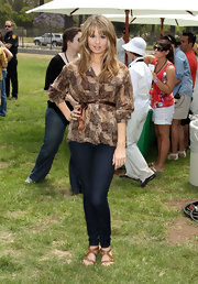 Debby Ryan paired her dark wash jeans with a brown abstract printed blouse.