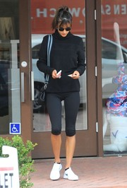 Alessandra Ambrosio paired a black turtleneck with capri leggings, both by Victoria's Secret, for her workout attire.