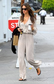 Alessandra Ambrosio kept it relaxed yet chic in a light gray jumpsuit, featuring a wrap-style bodice and a drawstring waist, while on a coffee run.