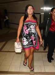 Amber Portwood looked ready for the beach as she arrived at the airport in a black and pink printed halter dress.