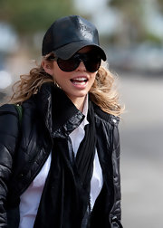 AnnaLynne attempts to go incognito with oversized black shades and a black leather trucker hat with asian symbols.