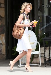 AnnaLynne showed off her spring style while out and about in hunky star Kellan Lutz. She paired her playful white dress with a bronzed tote bag.