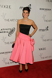 Marisa shows off her toned arms in this 80's inspired black and pink cocktail dress.