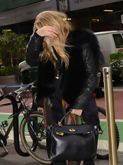 Ashley Olsen hid behind her long blonde locks carrying an oversized black leather tote with gold clasps.