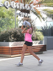 Ashley Tisdale hit the gym in a hot pink tank and skimpy black running shorts.