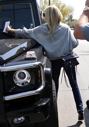 Ashley sported a hot blue leather shoulder bag with multiple zippers, black fringe and a gold chain strap while pulling a parking ticket off of her Mercedes. Oops!