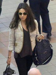 Mila Kunis arrived on a flight at LAX carrying a textured black leather tote by Givenchy.