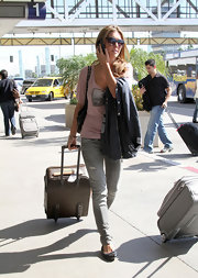 Even when she travels she travels in style with her lV luggage.