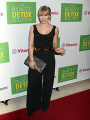 Hilary Duff teamed her black jumpsuit with a Goyard pochette.