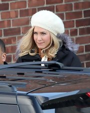 Jennifer Aniston covered up her new blond 'do with a white knit beanie while walking to set in Connecticut.
