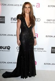 Britney Spears showed her glam side at Elton John's Oscar bash with a black gown with gold sparkles and a deep v-neck.
