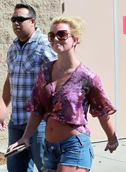 "Hanging out in L.A., Britney is wearing the ""Ga Ga Galore"" sunglasses. They are square brown glasses with a hint of purple that matches her blouse. These are good pair of sunglasses for her casual look."