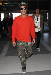 Bruno Mars opted for a plain red crewneck sweatshirt to pair with his camo cargo pants while leaving on a flight from LAX.