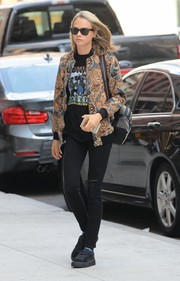 Cara Delevingne continued the rocker-chic vibe with a pair of slashed black jeans.