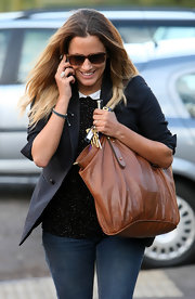 Caroline Flack gave her collegiate-inspired look an earthy vibe with a brown leather tote.