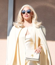 Lady Gaga sported a monochromatic leather clutch, cape, and dress combo on the set of 'American Horror Story: Hotel.'
