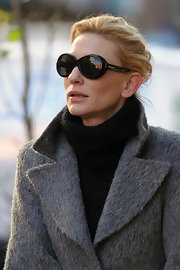 Cate Blanchett looks ultra sophisticated in her round black shades. She tops her look off with a sleek black turtle neck and grey wool over coat.
