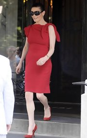 Catherine looked chic in a fitted red dress with a knotted shoulder detail.