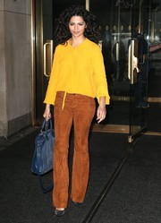 Camila Alves teamed her top with a pair of tan suede bell-bottoms by Alice + Olivia.