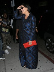 Kris Jenner's red crocodile clutch looked striking against her dark outfit.