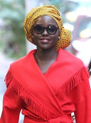 Lupita Nyong'o headed to 'Good Morning America' sporting a vibrant yellow head wrap and red coat combo.