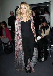Nicole opts for a daring fashion ensemble in a floral silk cape over her black ensemble.